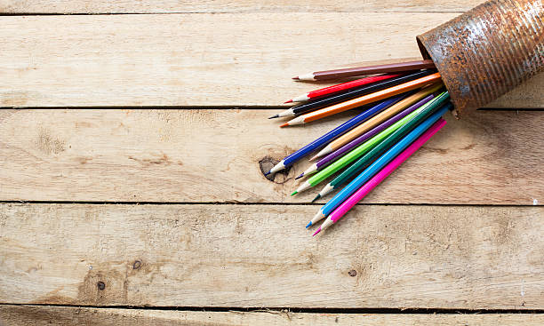 color pencils in rusty tin can, wood table stock photo