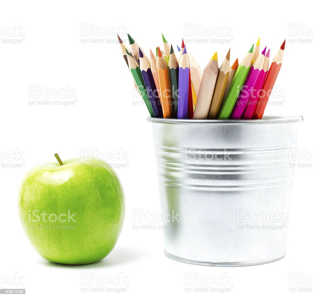 Color pencils in tin can or holders and green apple, royalty-free stock photo