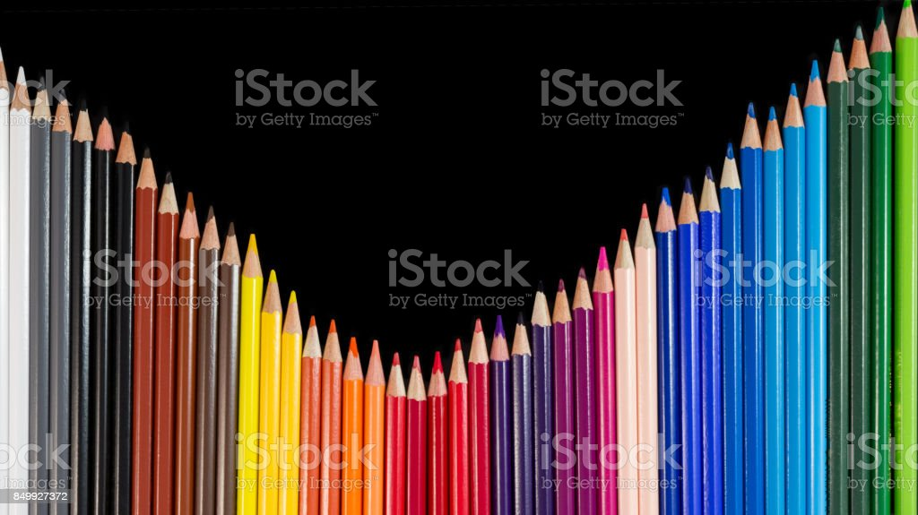 Color pencils in wave formation isolated on black background close-up stock photo
