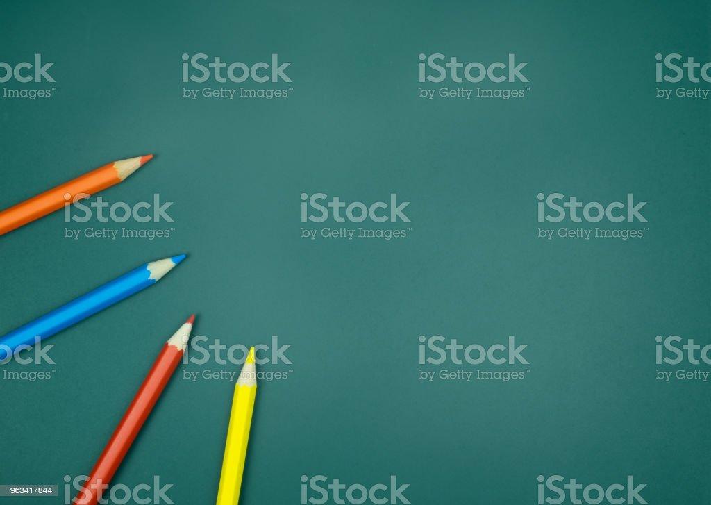 Color pencils on green chalkboard background - Zbiór zdjęć royalty-free (Aranżacja)