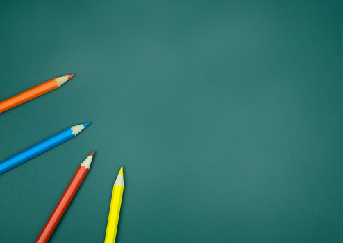 Color Pencils On Green Chalkboard Background - zdjęcia stockowe i więcej obrazów Aranżacja