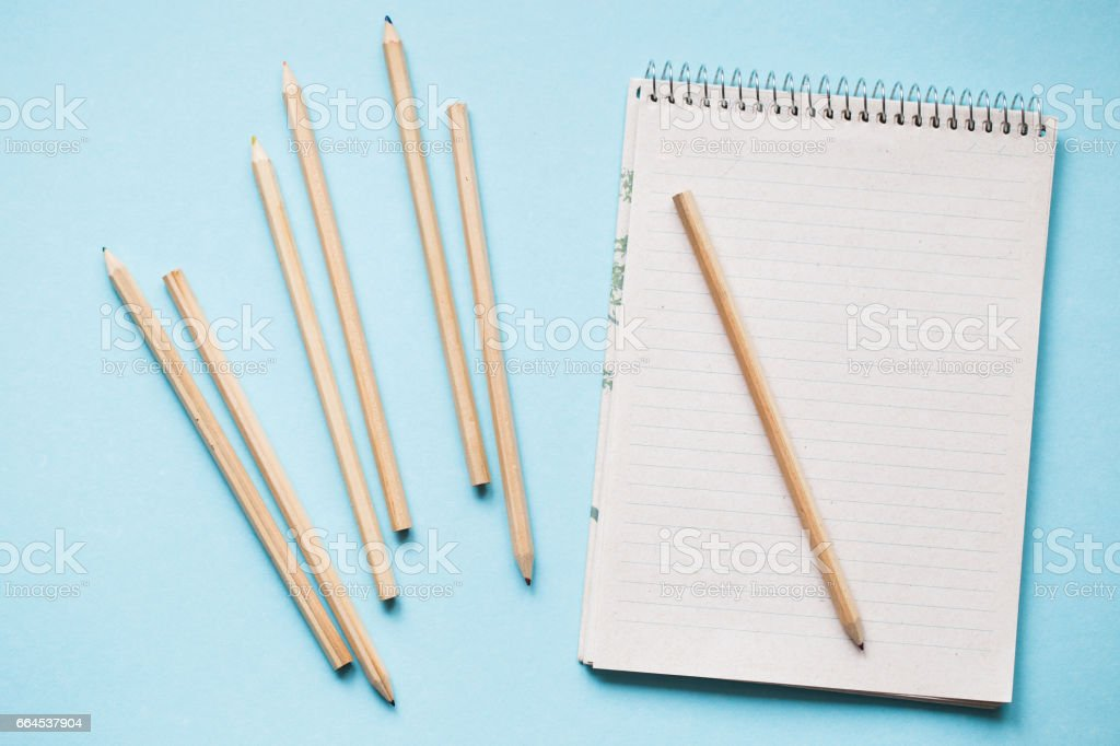 Color pencils on notebook on blue background royalty-free stock photo