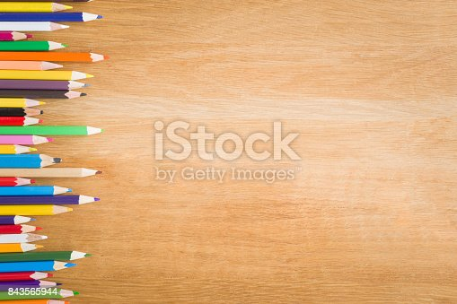 istock Color pencils on the wooden table. Art concept. Top view. Empty place for a text or drawing on the background. 843565944