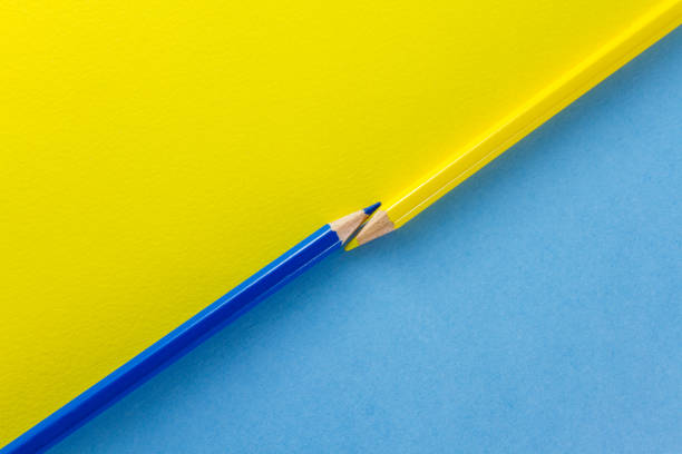 Color pencils on yellow and blue color papers arranged diagonally stock photo