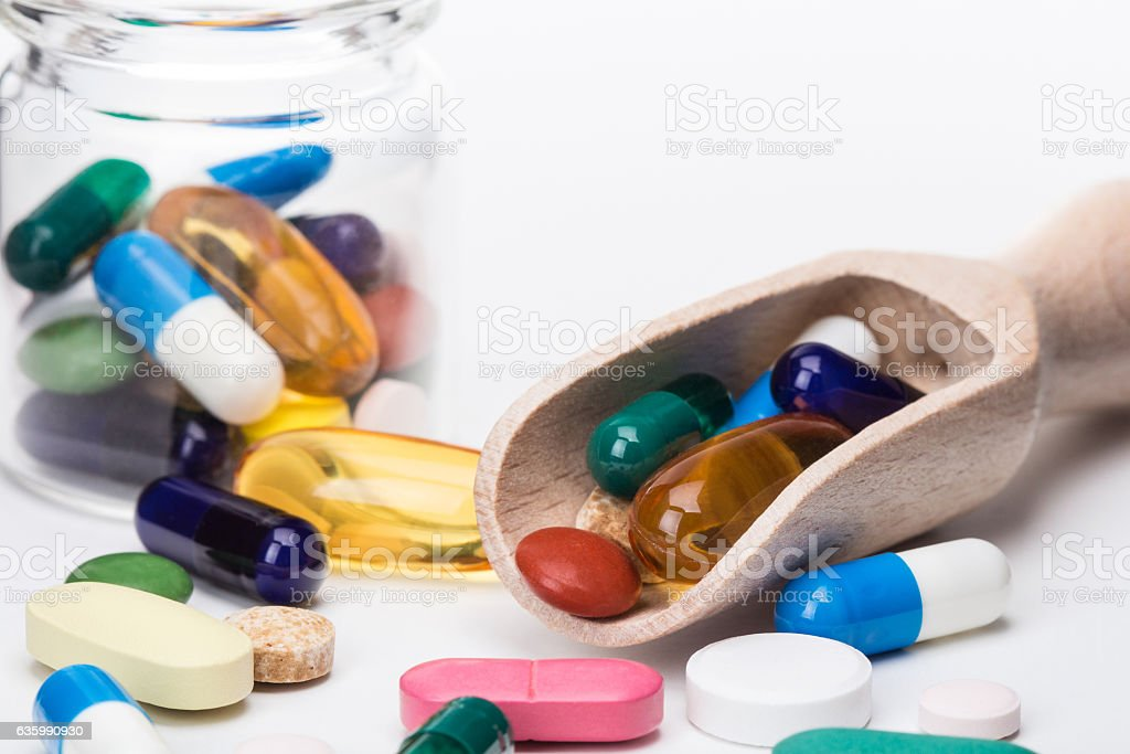 Color pills in glass container and wooden dispencer stock photo