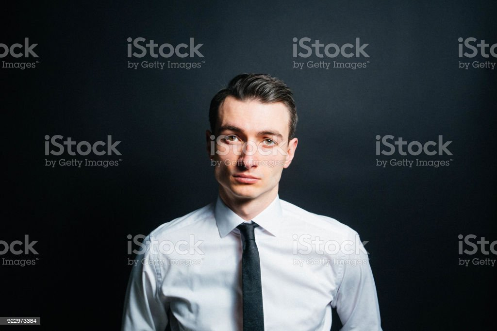 Color portrait of a young man in a shirt and black tie, seriously...