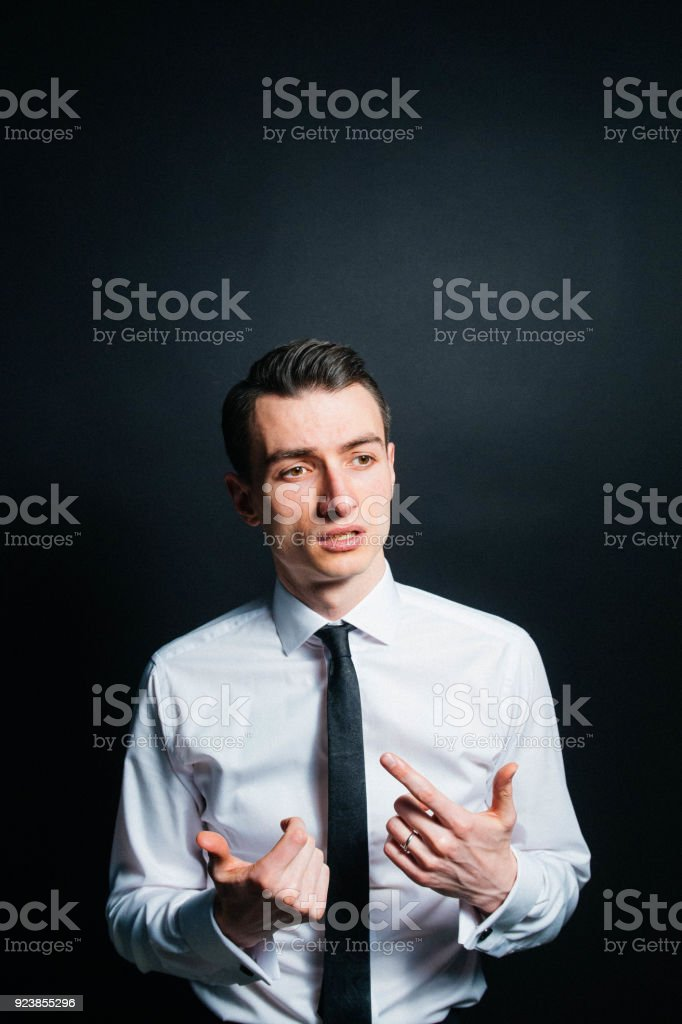 Color portrait of a young man in a shirt and black tie, talking and...