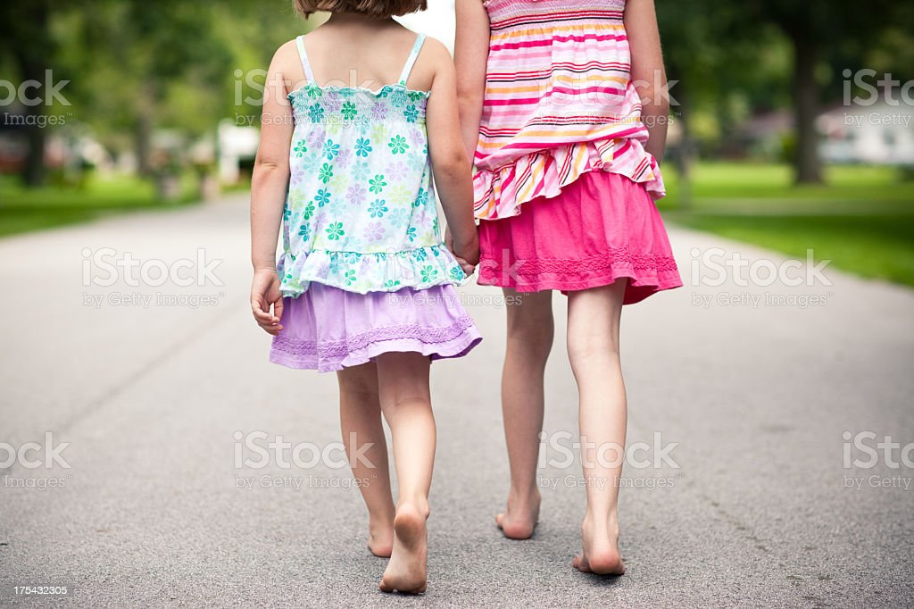 Color Portrait of Two Happy Sisters Walking Down the Street royalty-free stock photo