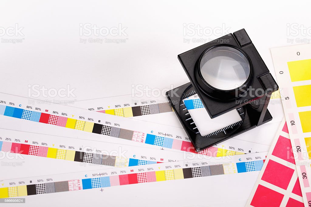 CMYK Color scales and loupe used for printing process stock photo