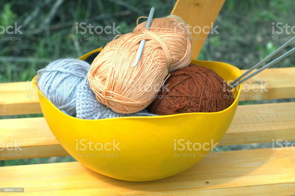 Color skeins of wool yarn, knitting needles and crochet hook in a big yellow bowl stock photo