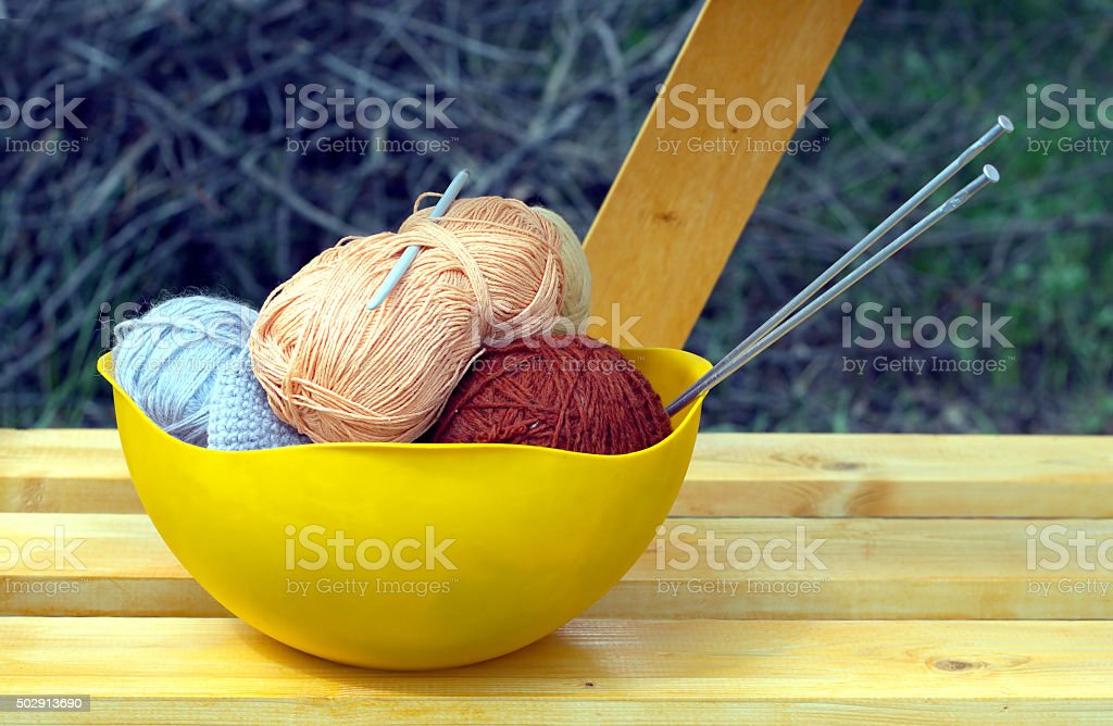 Color skeins of wool yarn, knitting needles and crochet hook stock photo