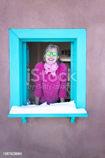 Color Surge: Stylish baby boomer with vibrant earrings and pink sweater leaning out a snowy turquoise window in adobe house. Copy space available.