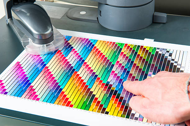 CMYK Color Swatch Chart with Spectrophotometer for Calibrating Printing Machines stock photo