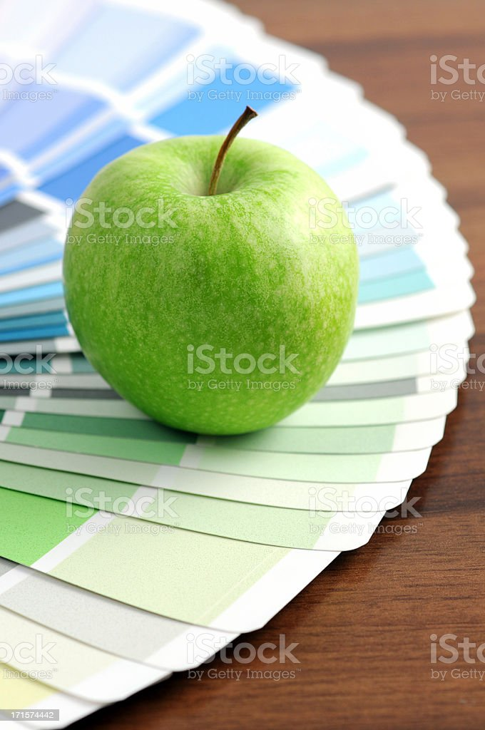 Color Swatch with green apple on brown table stock photo