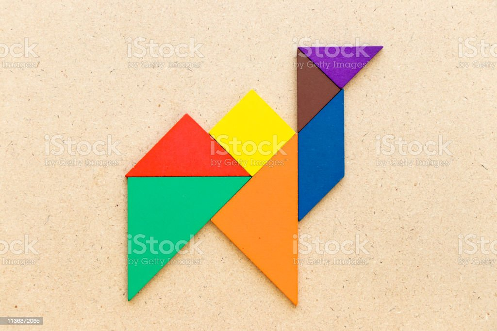 Color tangram in camel shape on wood background stock photo
