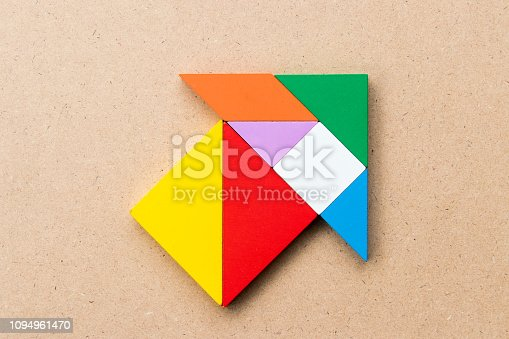 istock Color tangram puzzle in arrow or home shape on wood background 1094961470