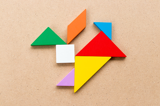 istock Color tangram puzzle in rabbit shape on wood background 1046888850