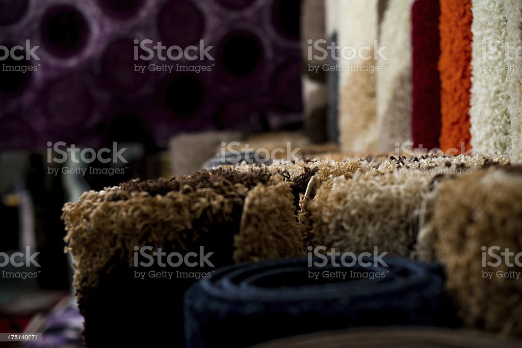 Colorful Collection Of Carpets And Rugs Folded And Displayed In Store