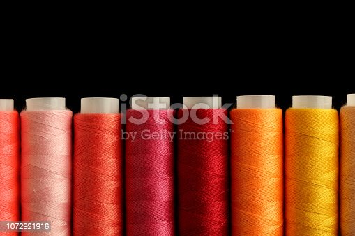 Color sewing threads on black background