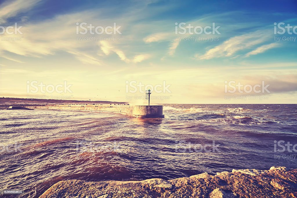 Color toned s sunset over port entrance beacon. stock photo