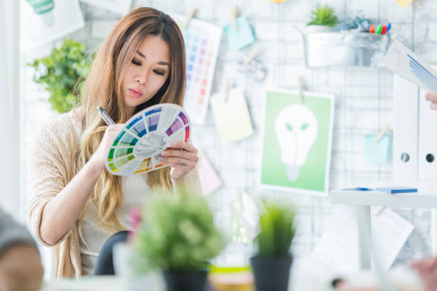 Color Wheel A multi-ethnic group of business-people are indoors in a design studio. They are wearing casual clothing. An Asian woman is choosing colors for a new project. illustrator stock pictures, royalty-free photos & images
