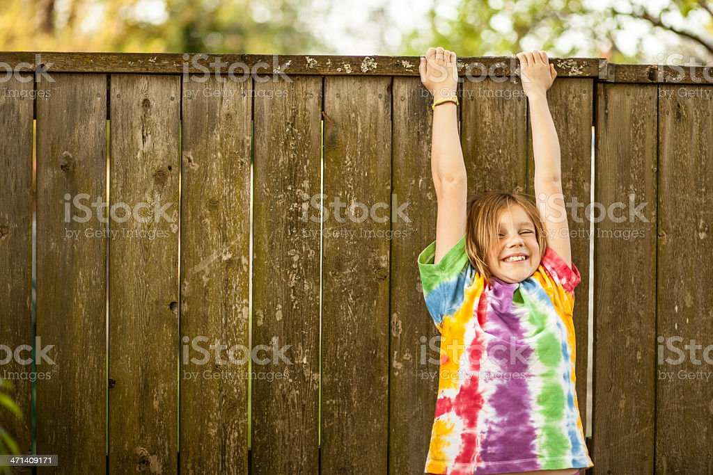 Color Young Girl in Tie Dyed T Shirt  Dangling Fence stock photo