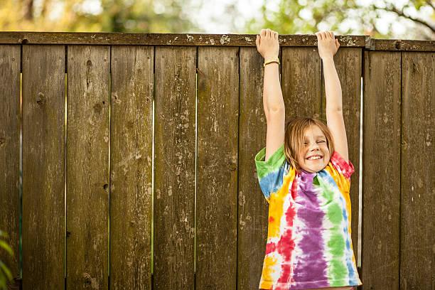 Farbe Junge Mädchen in Tie-Dye T-Shirt baumelt Zaun – Foto