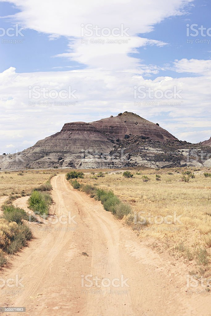 Colorado desert dirt road and sedimentary outcroppings royalty-free stock photo