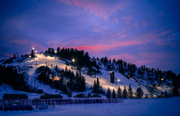 Colorado ski slope during blue hour in winter View of Colorado ski slope with running chairlift after sunset; blue hour in the mountains steamboat springs stock pictures, royalty-free photos & images