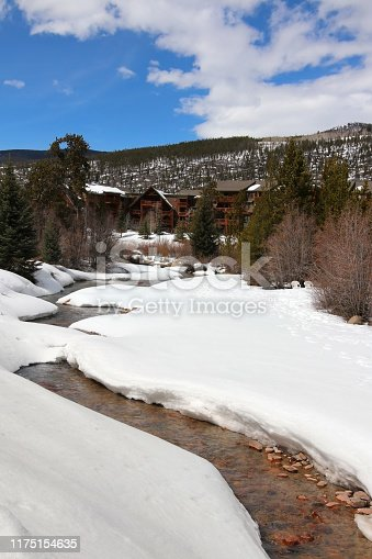 Scenic view with water stream on a covered by snow valley between rocky mountains. Amazing Keystone landscape, Colorado, USA.