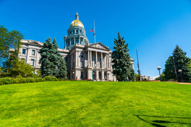 colorado state capitol building standing tall on green grass hill top - colorado state capitol stock photos and pictures