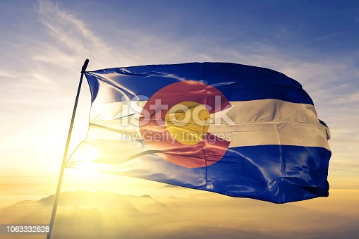 Colorado state of United States flag on flagpole textile cloth fabric waving on the top sunrise mist fog