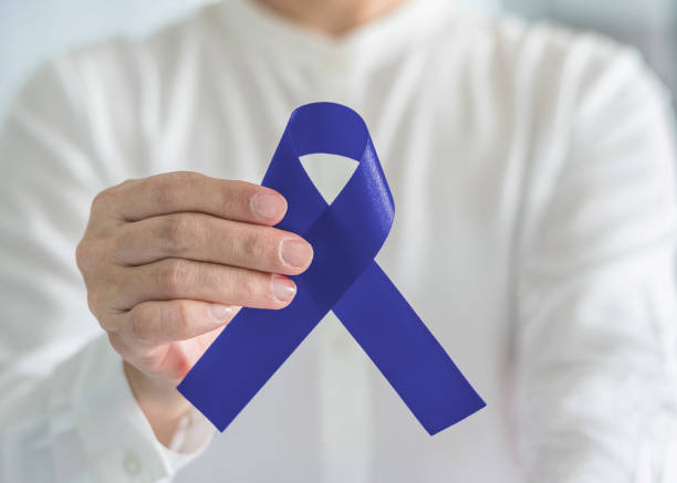 Colorectal Colon cancer awareness ribbon for men's health care concept with blue bow color in person's hand stock photo