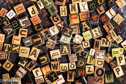 Color image depicting an overhead view of a large selection of colored alphabet letter tiles scattered, apparently haphazardly, across a rusty metal surface.