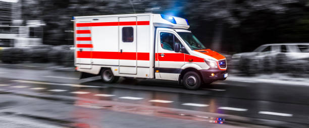 colored ambulance car speeding in black and white stock photo