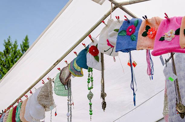 farbige baby-caps hängen am seil village fair - kindermütze häkeln stock-fotos und bilder