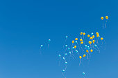 colored balloons rise to the clear blue spring sky