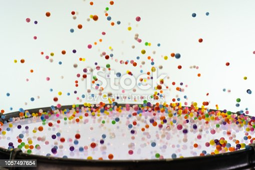 1131535585 istock photo Colored balls bounces off drum in shockwave pattern. White background. 1057497654