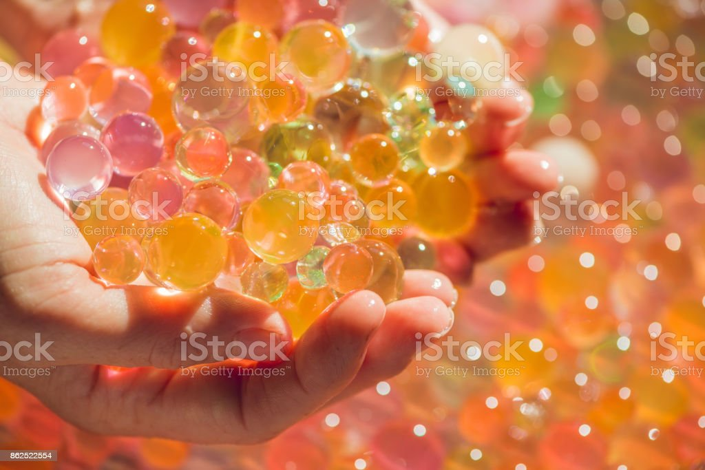 Colored balls of water beads, hydrogel in in hands. Sensory experiences stock photo