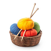 Colored balls of yarn with knitting needles in basket on white background.