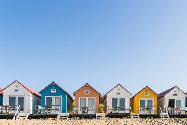 Colored beach houses in a row Along the beach of The Netherlands you can find lots of colored beach houses. They are occupied by tourists who stay there for the weekend or spen their holiday there beach hut stock pictures, royalty-free photos & images