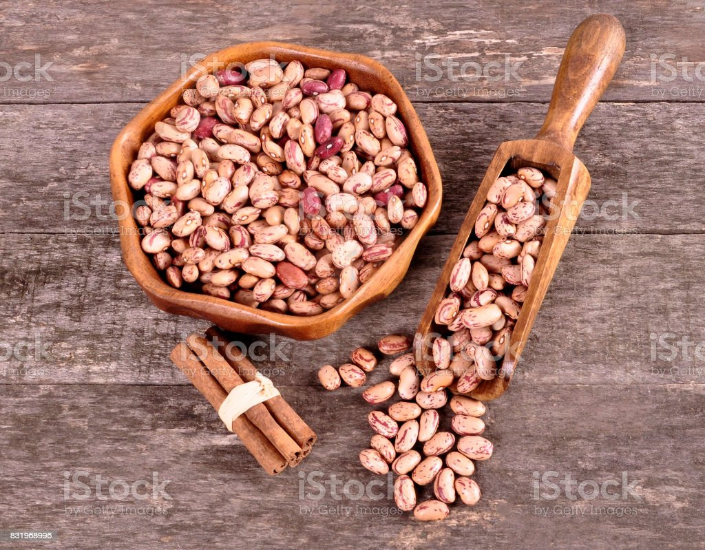 Colored beans in a wooden bowl on an old wooden background stock photo