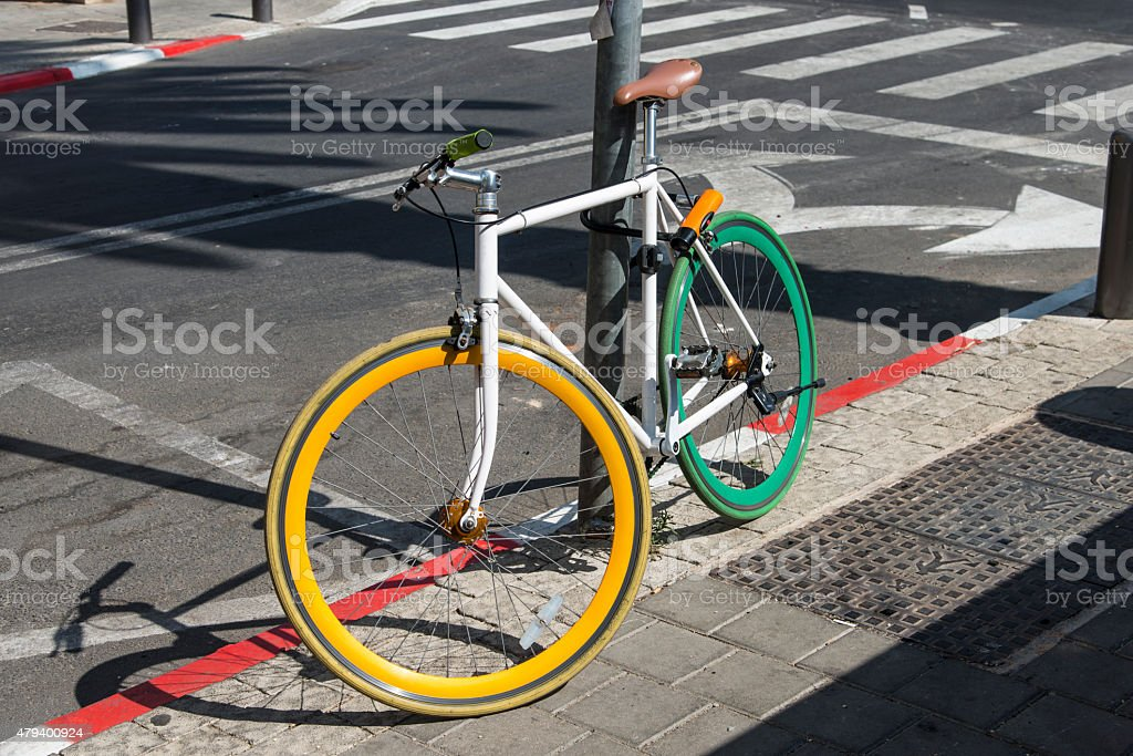 colored bicycle locked to a post on the pavement stock photo