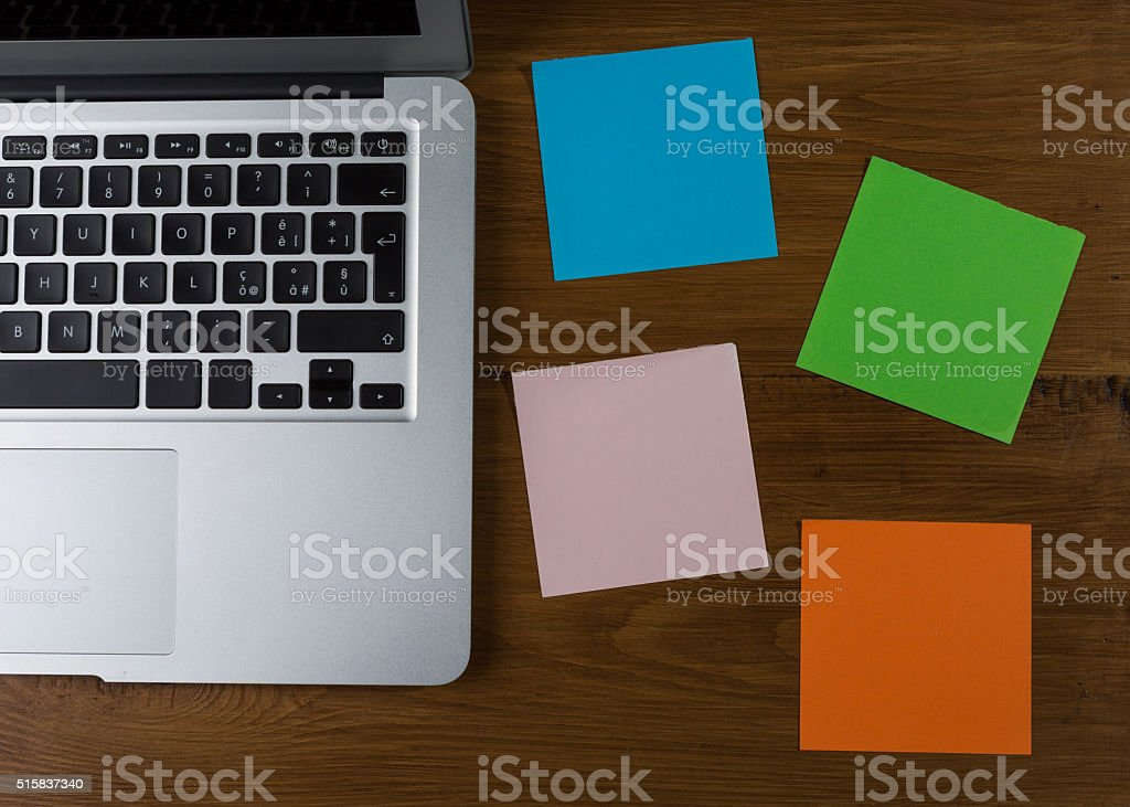 Colored blank post-it with office supplies on wooden table. stock photo