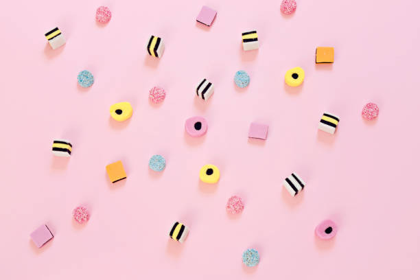 Colored candy scattered on the pink background stock photo