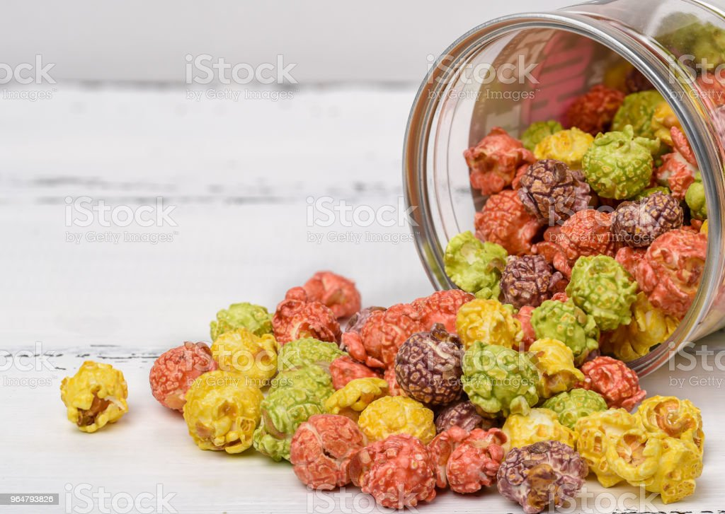 Colored caramel popcorn scattered on a white wooden background. royalty-free stock photo