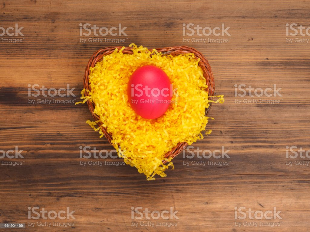 Colored chicken egg on background of bright yellow straw and old wooden table. The view from the top foto stock royalty-free