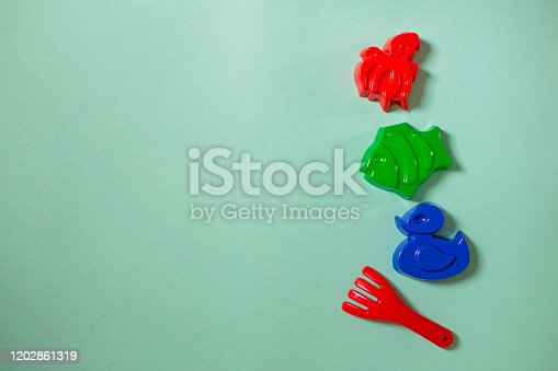 Bright colored children's sand molds on light green background