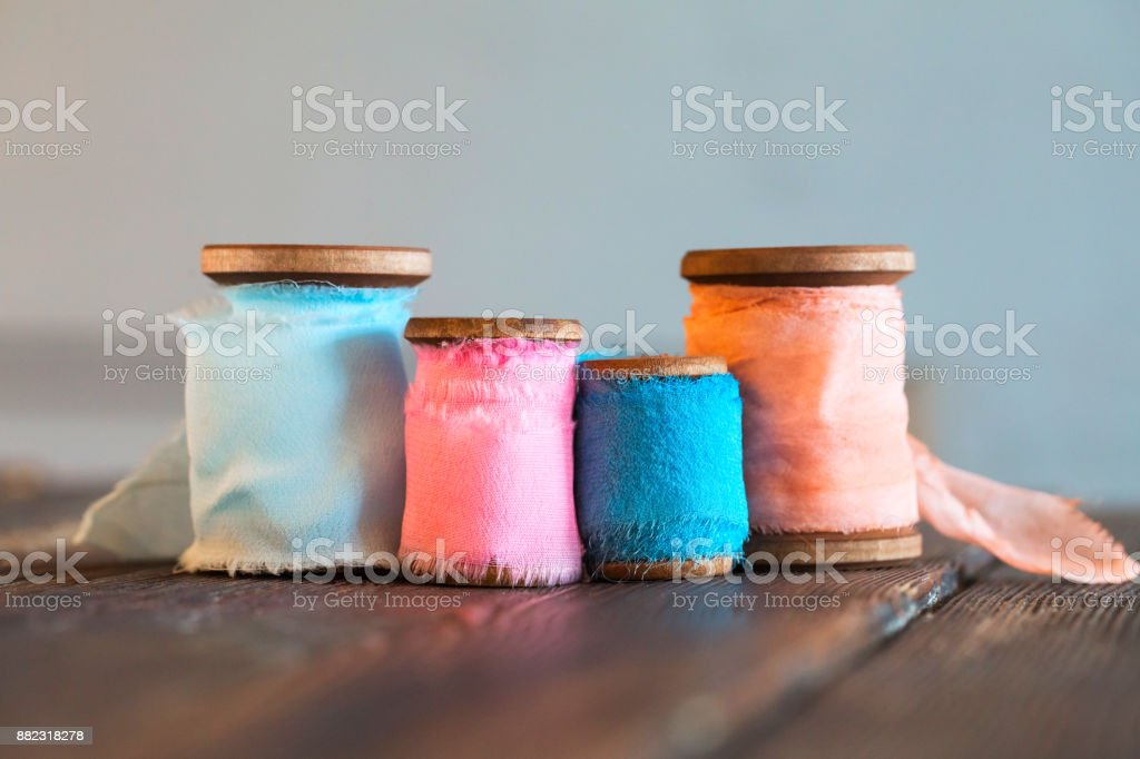 Colored coils of colored cotton ribbons on wooden surface stock photo