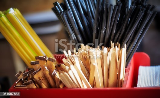 Close-Up Of Colored Drinking Straws, Sugar in Bags and Stirrers At Bar Counter